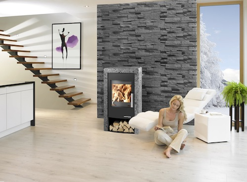 """""""Pyrus"""" ist mit einem zusätzlichen Speicherstein ausgestattet und kann die Wärme bis zu zehn Stunden halten. Die Naturstein-Variante """"Serpentino"""" wirkt in Kombination mit dem großen Sichtfenster und dem praktischen Holzfach sehr elegant. (Foto: epr/Haas+Sohn)"""