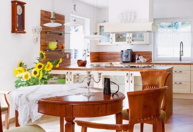 Die herzliche Atmosphäre setzt sich auch im Innenbereich fort. Den großzügigen Wohn-Ess-Kochbereich dominieren Möbel und Wandpaneele aus rötlichem Holz. (Foto: epr/SchwörerHaus)