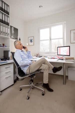 Wo gehobelt wird, da fallen Späne. Viele rollen zum Beispiel im Home Office  oft telefonierend zwischen Aktenschrank und Schreibtisch auf dem Teppichboden hin und her. Damit dieser das lange mitmacht, ist die richtige Verlegart entscheidend. Ein lose liegender Teppichboden verrutscht unter der Stuhlrollenbelastung oder bildet Wellen und Beulen. Wird er aber fest auf den Untergrund geklebt, bleibt er an seinem Platz und über viele Jahre gut in Form. Foto: IBK – Initiative Bodenbeläge kleben