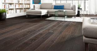 Holz eröffnet viele Gestaltungsmöglichkeiten. Ein dunkler und intensiv gemaserter Holzfußboden setzt einen klaren Kontrast zu den hellen Möbeln und Accessoires im Wohnzimmer. Dadurch entsteht ein sehr edles, repräsentatives Ambiente.  Bild: tdx/GD Holz e.V./HARO