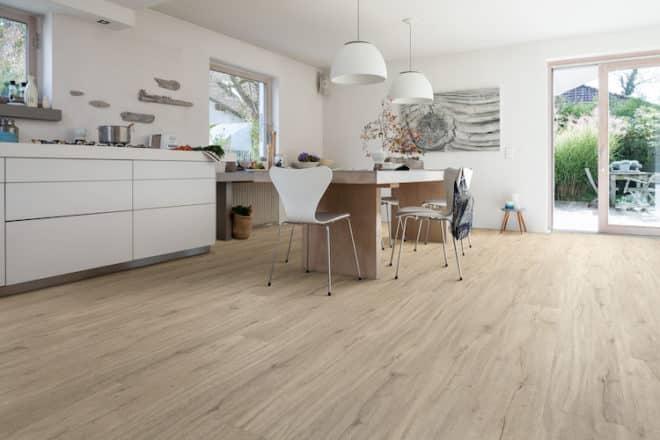Küche, Essplatz und Wohnzimmer gehen in modernen Grundrissen fließend ineinander über. Für eine großzügige Raumwirkung sollte dafür ein einheitlicher Bodenbelag gewählt werden. Designböden werden den unterschiedlichen Ansprüchen gerecht: Sie sind strapazierfähig und leicht zu reinigen wie Laminat und dennoch fußwarm und komfortabel wie Parkett. Bild: tdx/HARO