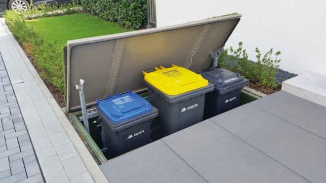 Werden die Mülltonnen nicht gebraucht, verschwinden sie in nur acht Sekunden im unterirdischen Mülltonnenhaus. Dazu öffnet eine integrierte elektrische Hebevorrichtung automatisch den Deckel und befördert die Müllboxen via Fernsteuerung oder Wandschalter auf Erdniveau. (Foto: epr/trafik up)